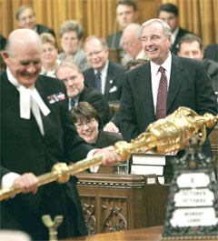 Canadian Sergeant-at-arms Gus Cloutier holding the  to open a sitting of the  with   in background (/)