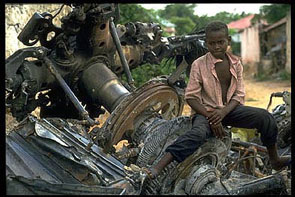 A Mogadishu boy straddles the remains of a US Black Hawk helicopter during the 1992-1995 UN peacekeeping operation