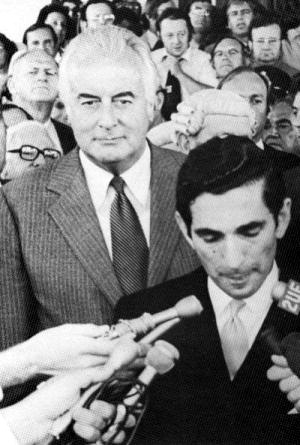 Whitlam listens to the proclamation of the dissolution of Parliament following the dismissal of his government on  . The proclamation is being read by , official secretary to the Governor-General. In the crowd behind Whitlam and Smith can be seen the politicians , ,  and .