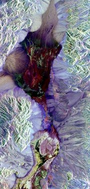 This False-color radar image shows central Death Valley and the different surface types in the area. Radar is sensitive to surface roughness with rough areas showing up brighter than smooth areas, which appear dark. This is seen in the contrast between the bright mountains that surround the dark, smooth basins and valleys of Death Valley. The image shows Furnace Creek  (green crescent feature) at the far right, and the  near Stove Pipe Wells at the center. (NASA image)