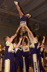 A cheerleader is flipped upside-down during a pep rally routine before a football game.