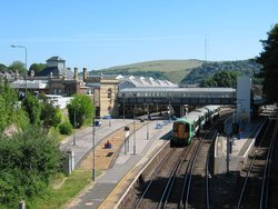 The modern non-terminus Lewes Station in ,  serves trains passing through the station.  Passengers reach the island platform (on right) by a pedestrian footbridge.
