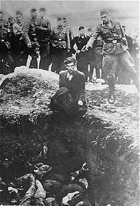 A member of Einsatzgruppe D executes a Jew kneeling before a filled mass grave in Vinnitsa, , in 1942.