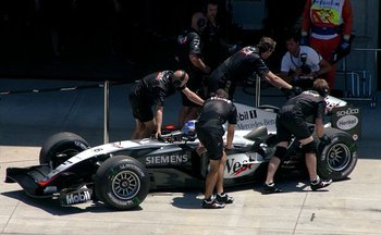 Members of the McLaren Formula One team push driver 's car into the garage during qualifying for the  at  in 2004