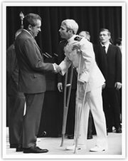 President Nixon greets released POW (and future Republican Senator) Navy officer  (on crutches) after years of imprisonment in North Vietnam, 1973.