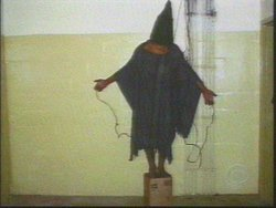 One of a series of photos taken by U.S. soldiers of Iraqi prisoners in Abu Ghraib. The hooded prisoner had wires attached to both hands and his penis, and was reportedly told that he would be electrocuted if he fell off the box he was standing on; the wires were not actually electrified.