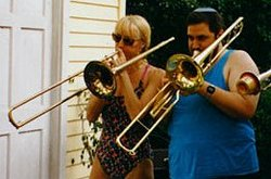 Musician on left with slide trombone; on right with valve trombone.