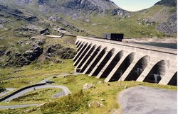 The upper reservoir and dam of the Ffestiniog Pumped-Storage Scheme in north .The power station at the lower reservoir has four water turbines which can generate 360 megawatts of electricity within 60 seconds of the need arising. The water of the upper reservoir (Llyn Stylan) can just be glimpsed on the right.
