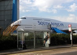 One of the challenges of intermodal transport is changing between modes. Despite proximity, transfers can be difficult. Such irony is illustrated by this bus stop inside the grounds of London (Heathrow) Airport, England. The aircraft is a South African Airways Boeing 747
